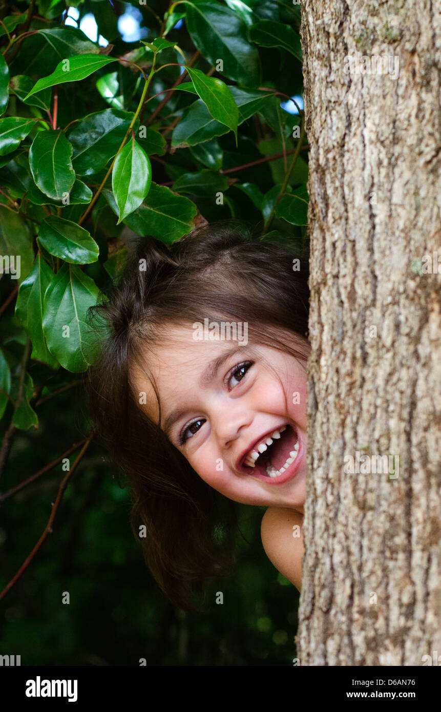 Cute little girl is playing hide and seek outdoors. - Stock Image