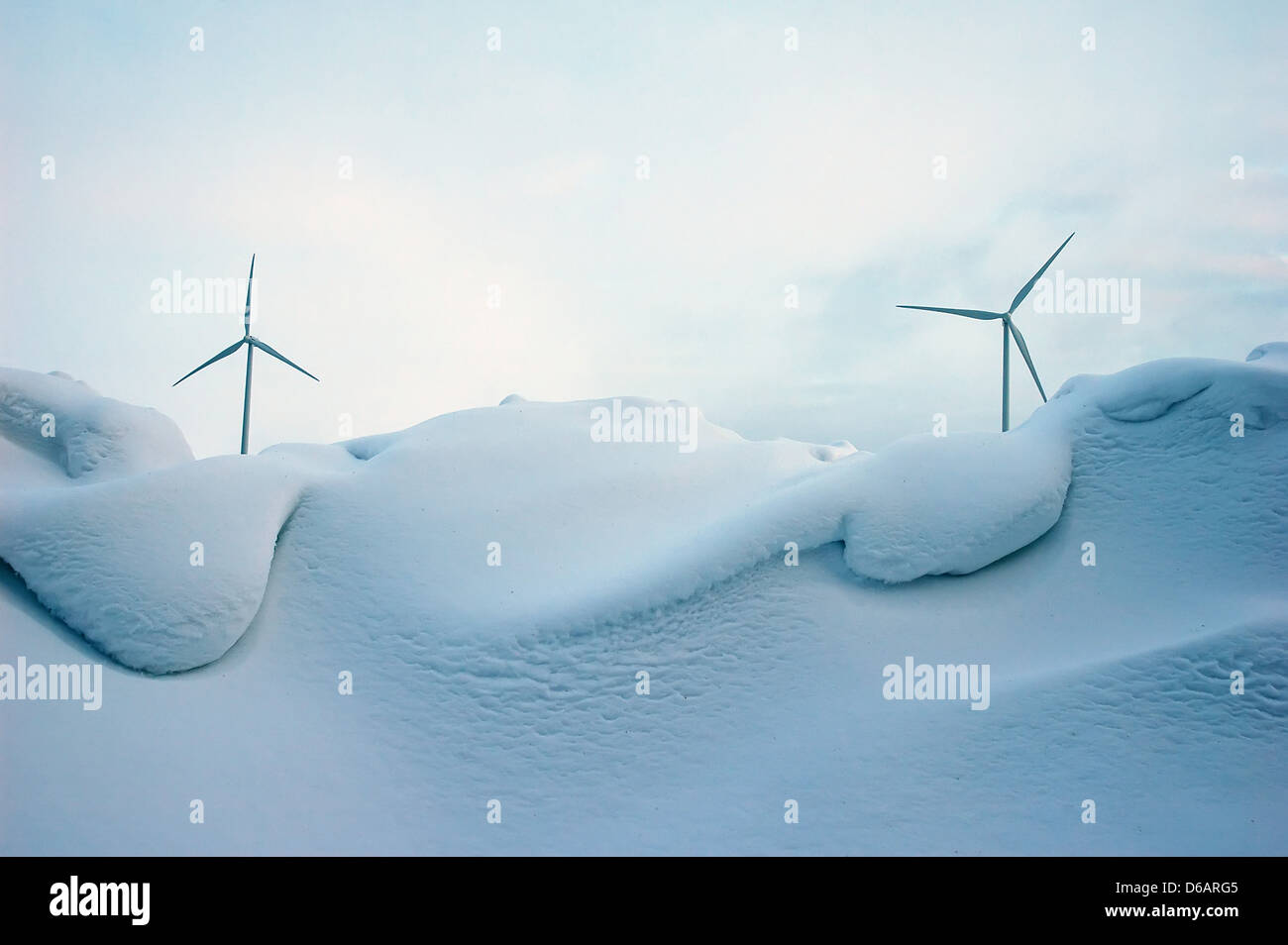 wind turbine generating electricity behind of snowdrift - Stock Image