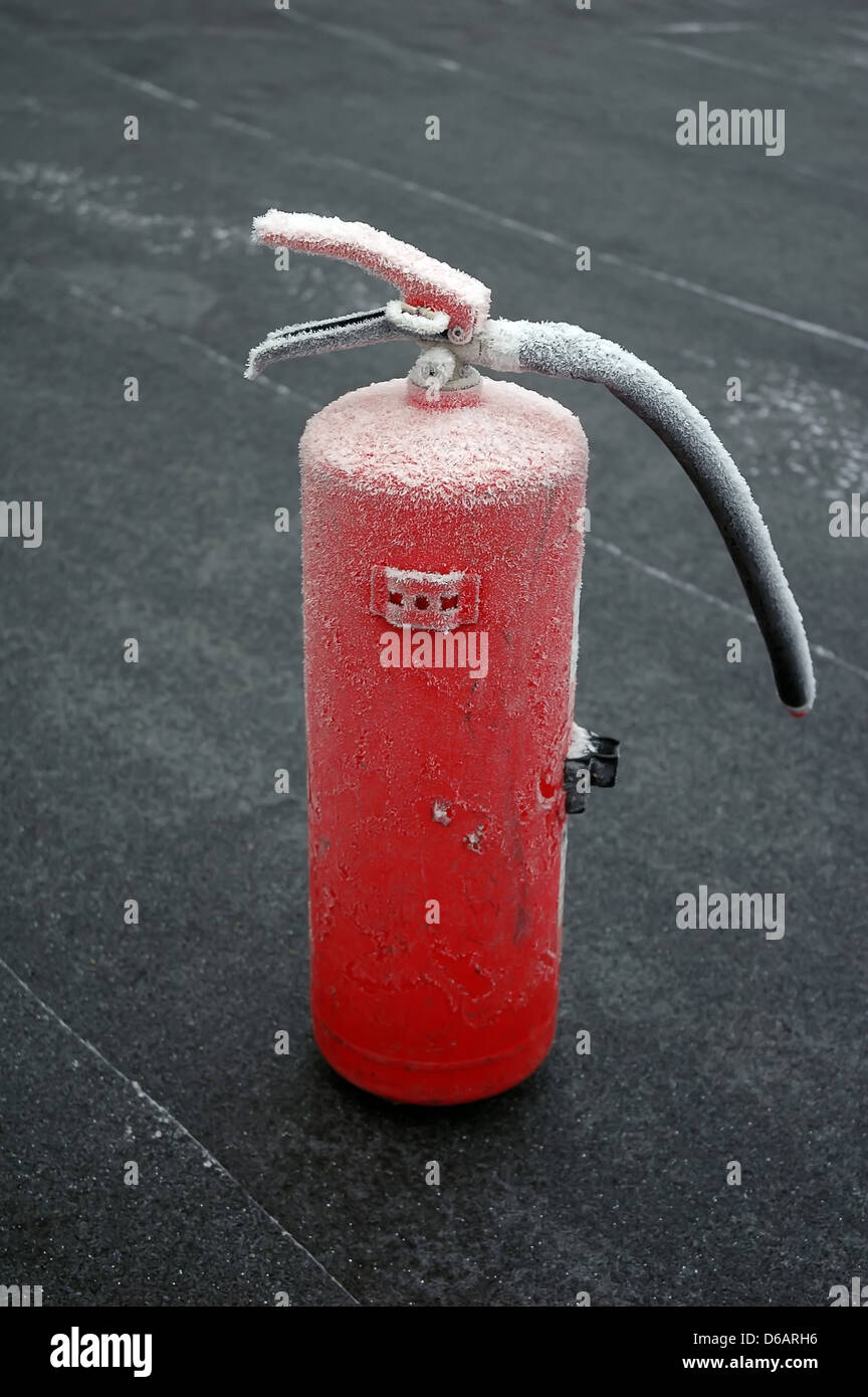 frosted fire extinguisher on floor - Stock Image