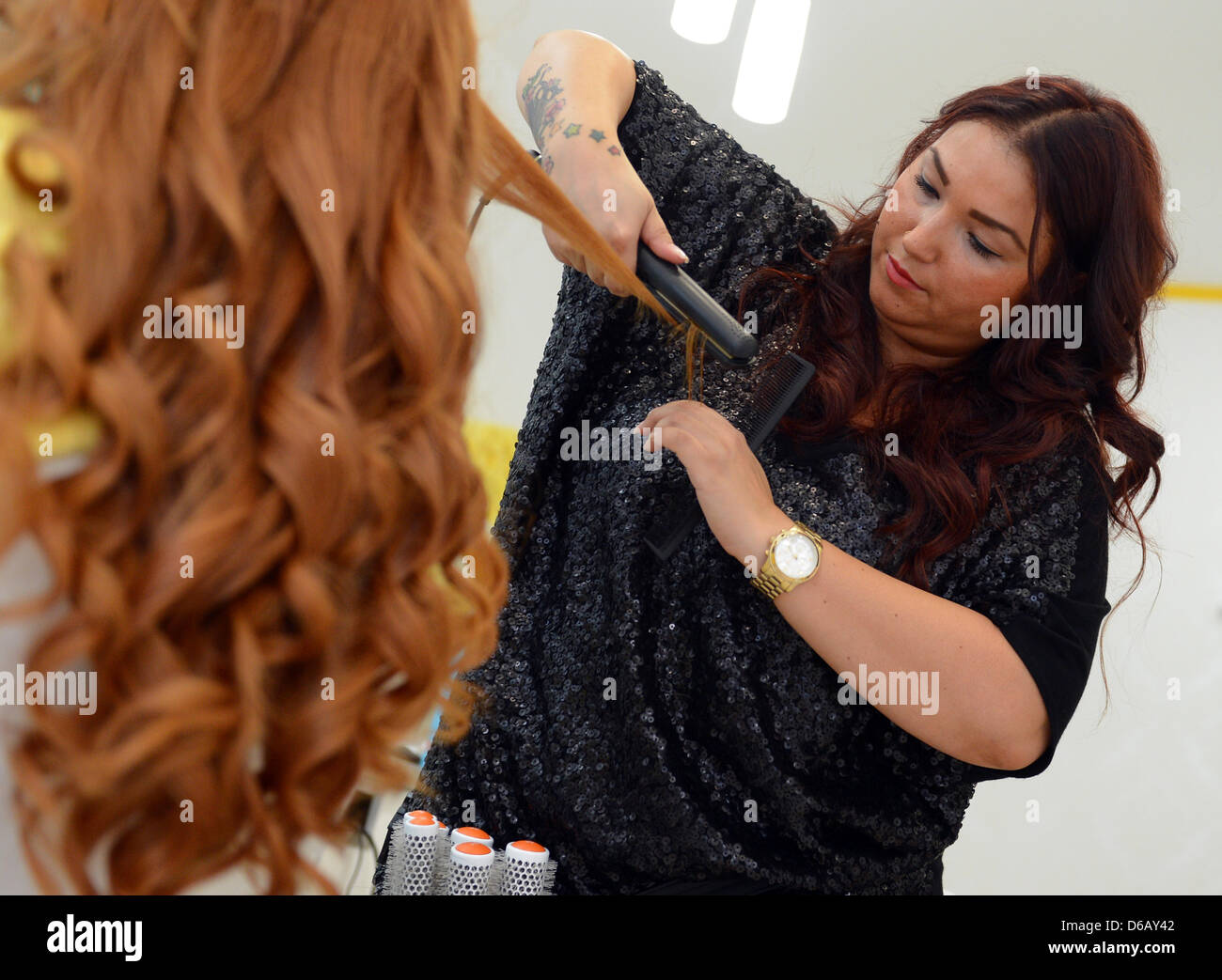 Hair dresser Arzu styles hair of a customer at the Dry Bar in Berlin ...