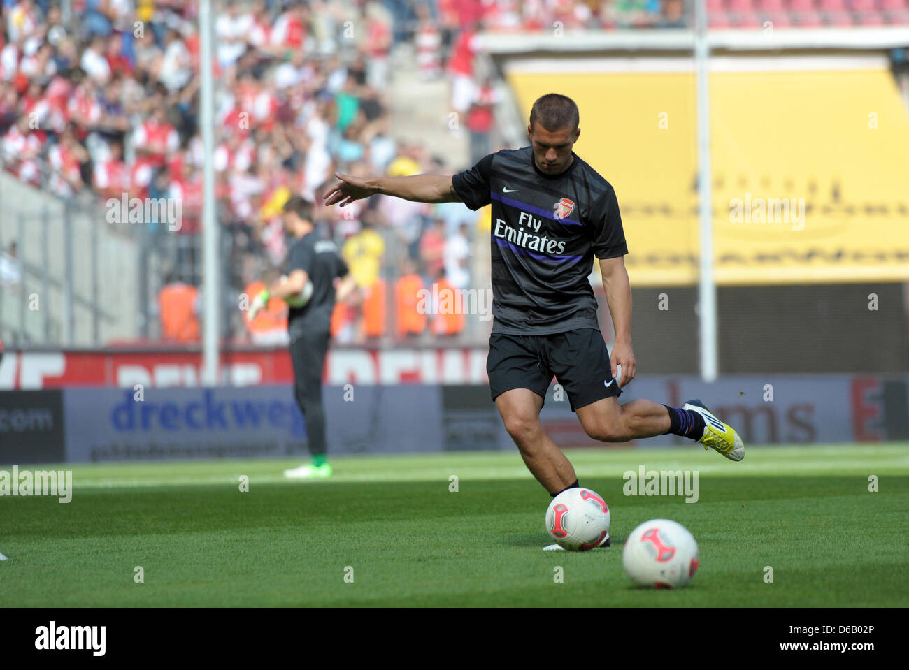 Arsenal's Lukas Podolski warms up before the soccer test match between 1. FC Cologne and FC Arsenal at the RheinEnergieStadion - Stock Image