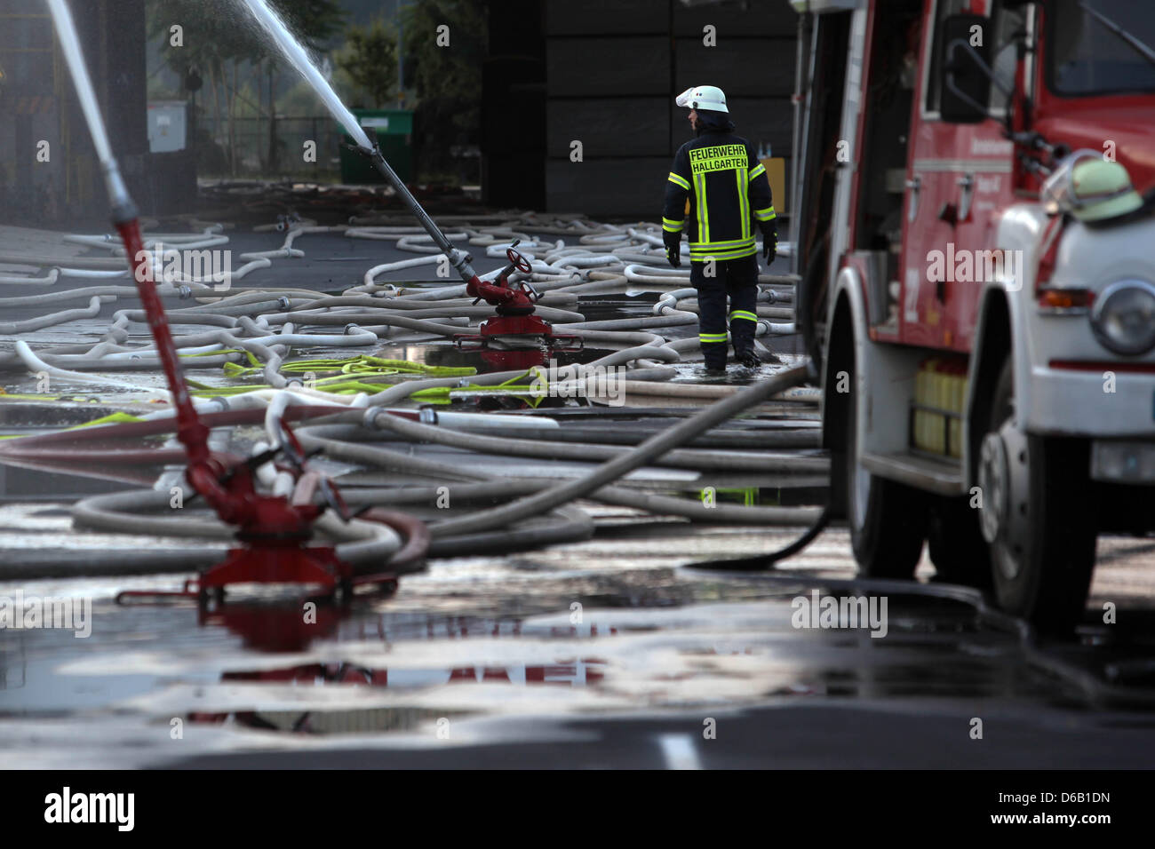 Numerous hoses sprinkle a hall of a foam factory where a poison gas accident caused large scale operation in Oestrich - Stock Image