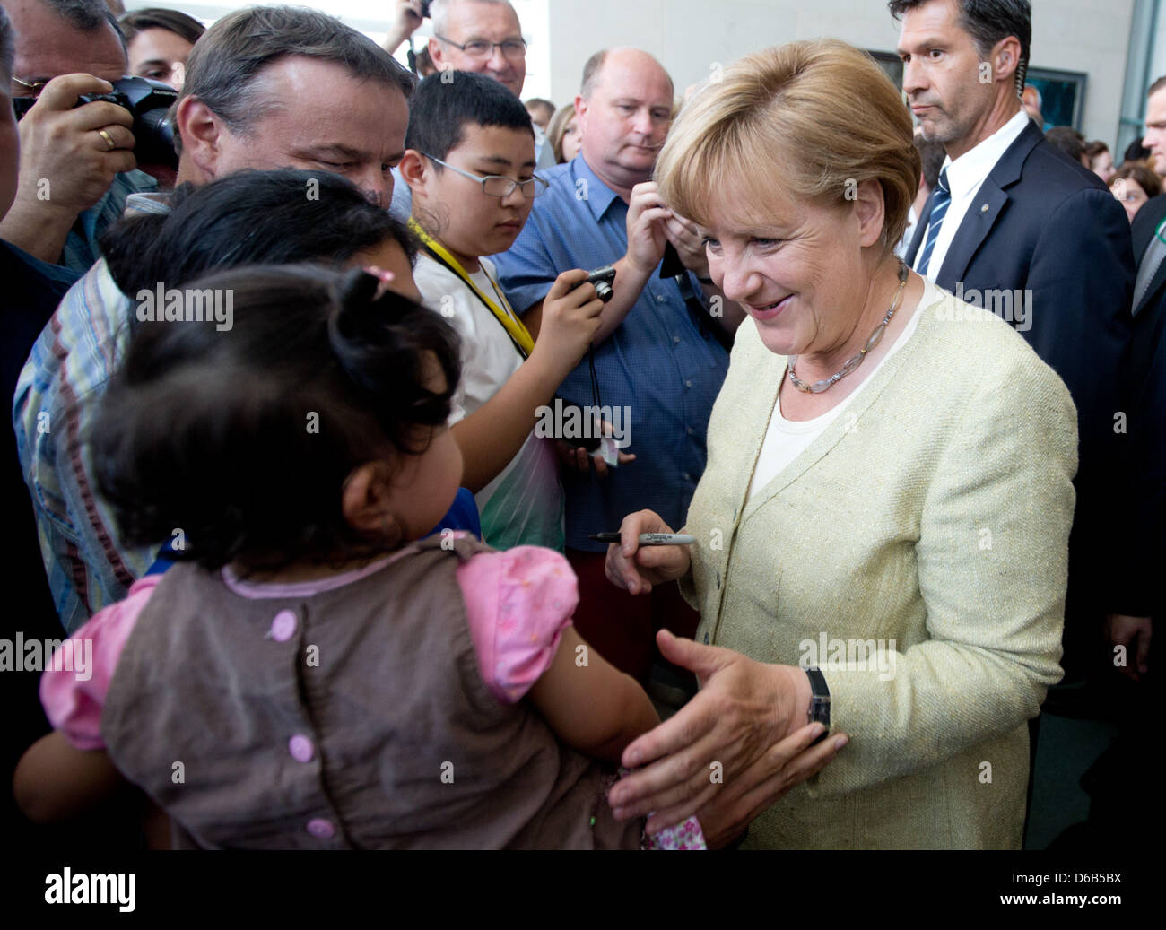 German Chancellor Angela Merkel signs autographs and talks to visitors at the Federal Chancellery in Berlin, Germany, Stock Photo