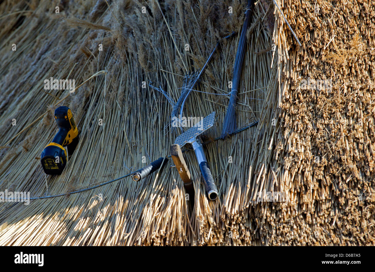 A thatchers tools are pictured on the thatched roof of an old farmhouse in Hoben near Wismar, Germany, 13 August - Stock Image