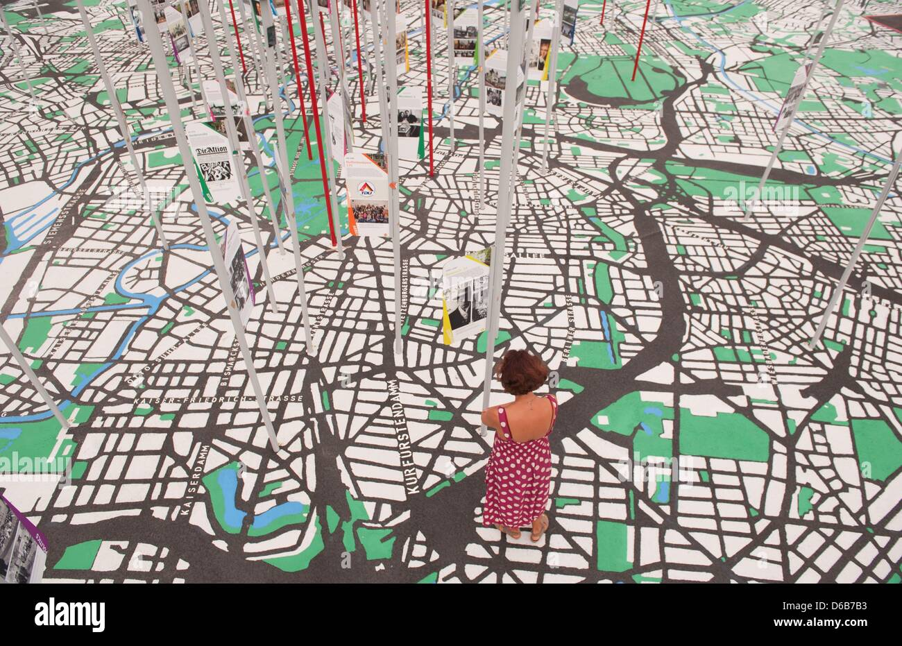 Exhibition Stand Location Map : A visitor stands among giant on an over sized map of