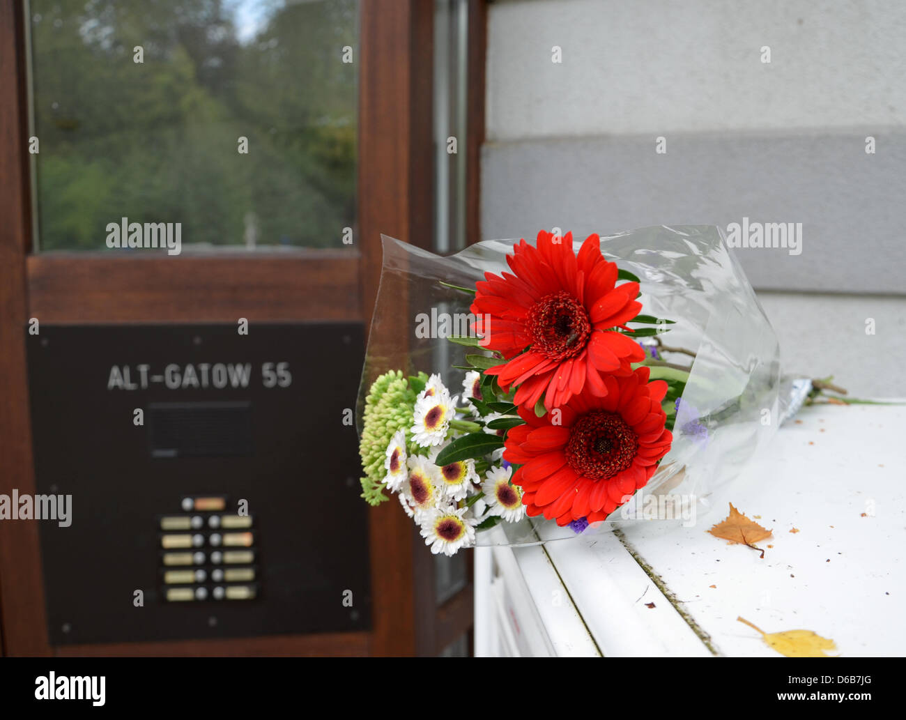 A flower bouquet lies in front of a house where a man supposedly killed his wife and two sons before committing - Stock Image