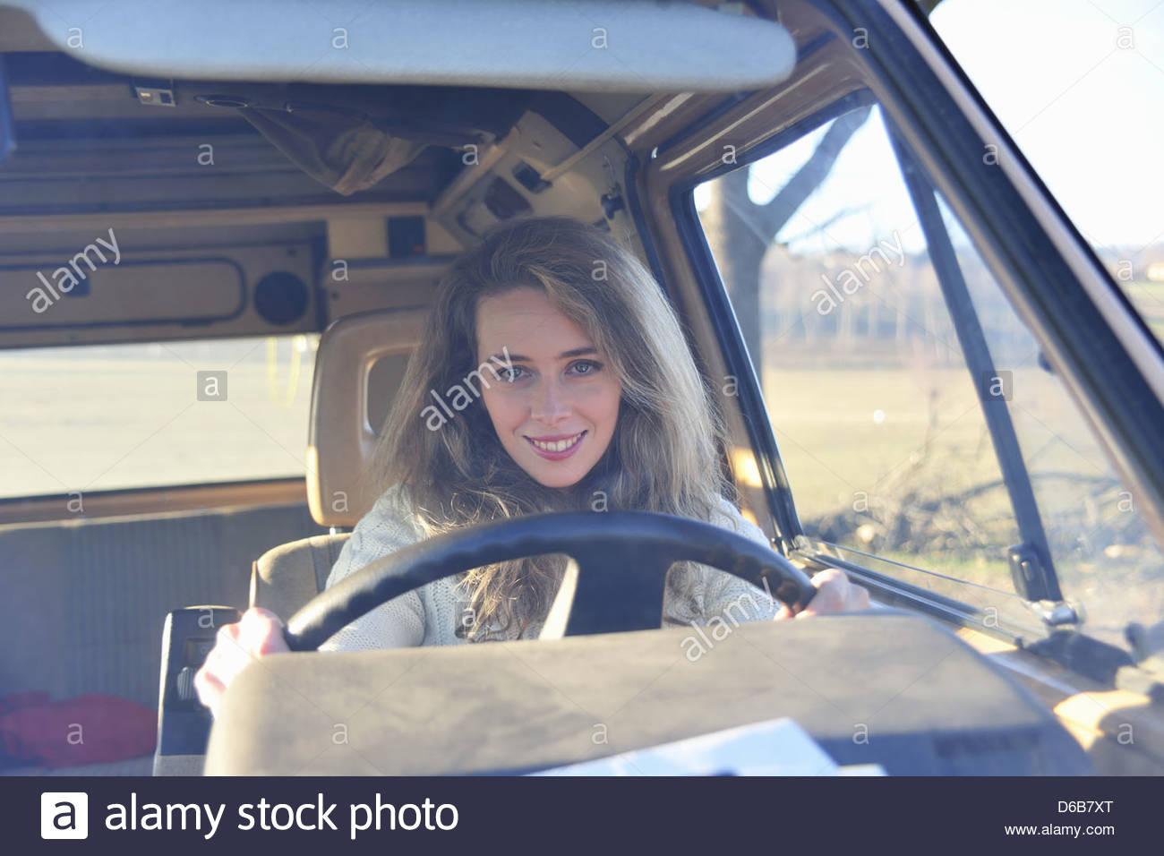 Smiling woman driving van - Stock Image