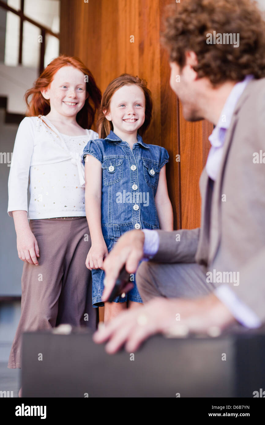 Businessman saying goodbye to daughters - Stock Image