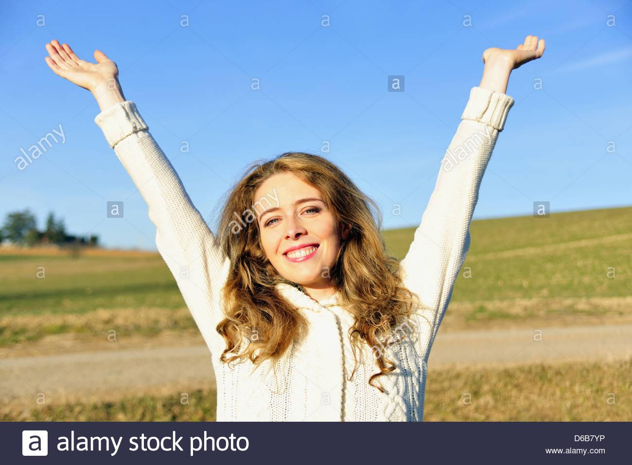 Woman cheering in rural field - Stock Image