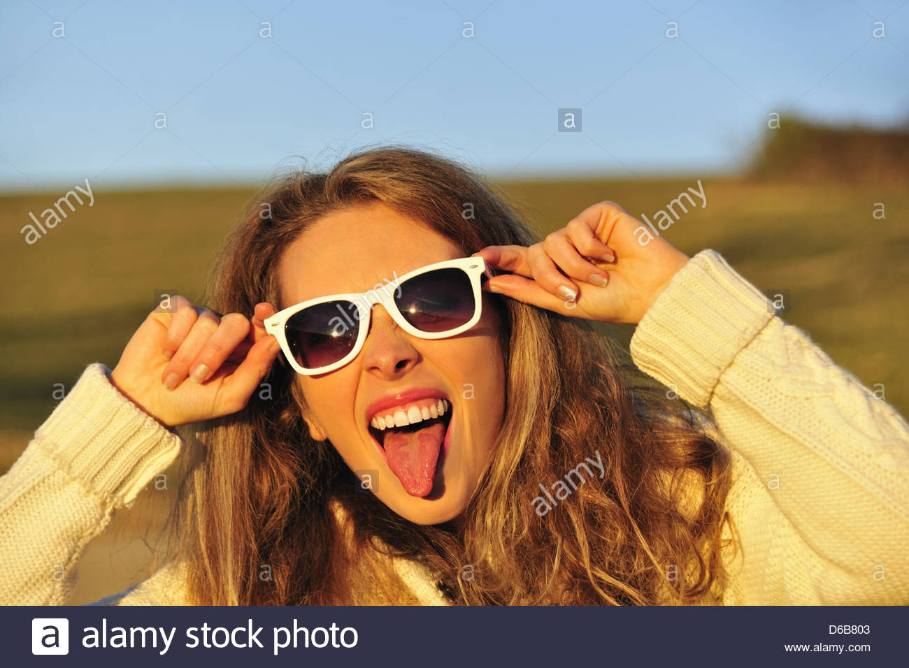 Woman in sunglasses in rural field - Stock Image