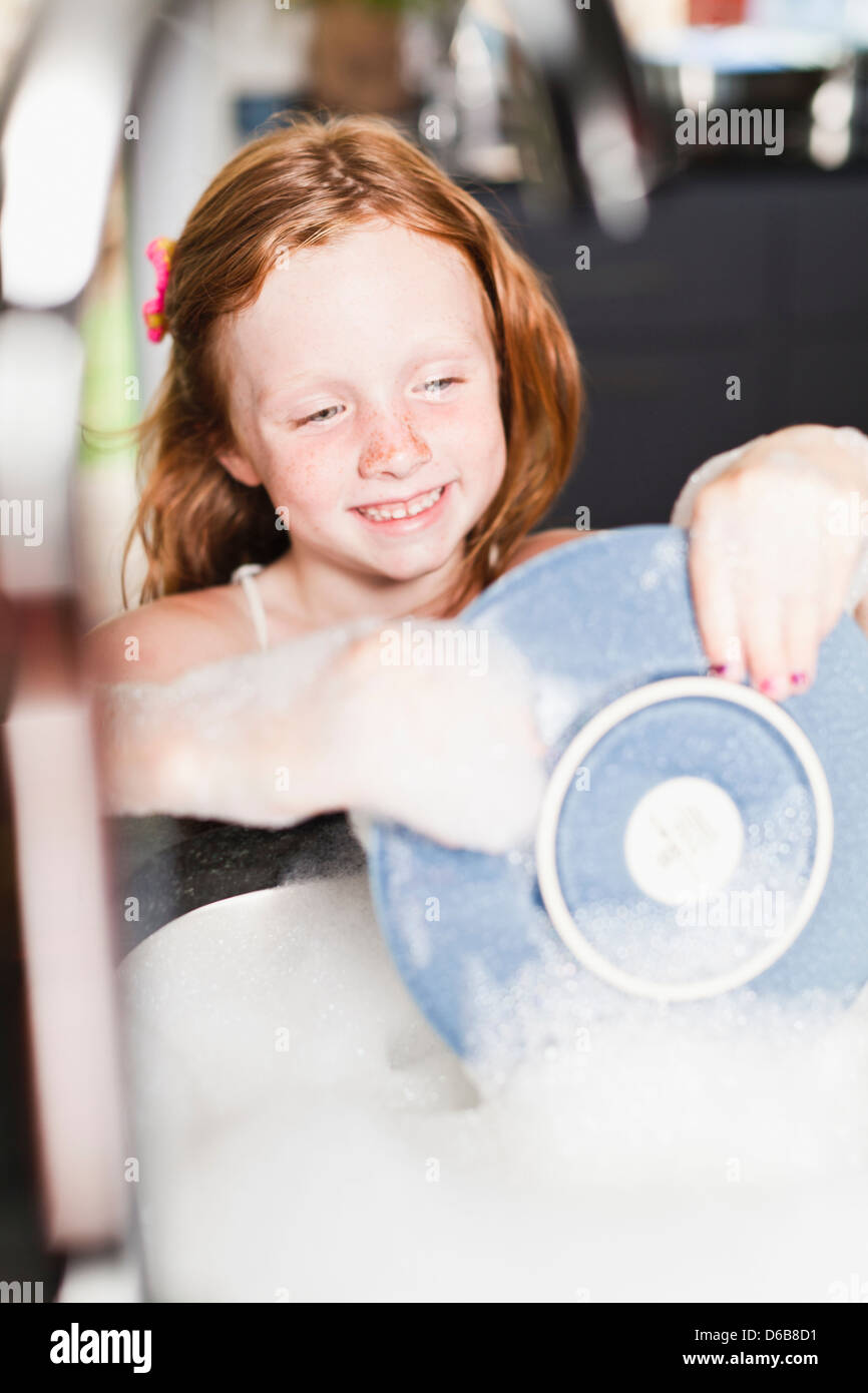 Smiling girl washing plate in sink - Stock Image