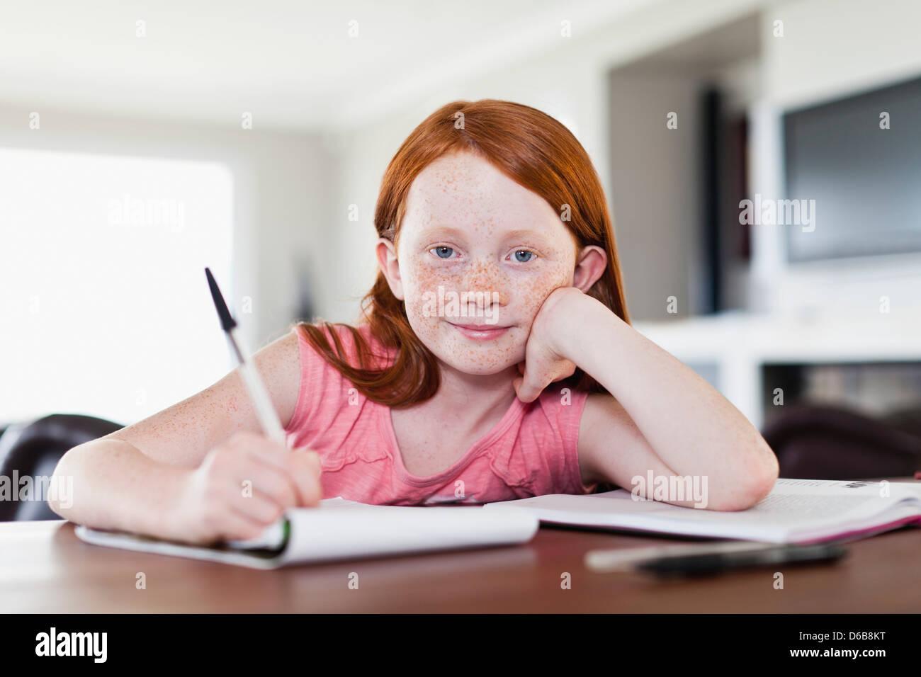 Smiling girl doing homework - Stock Image