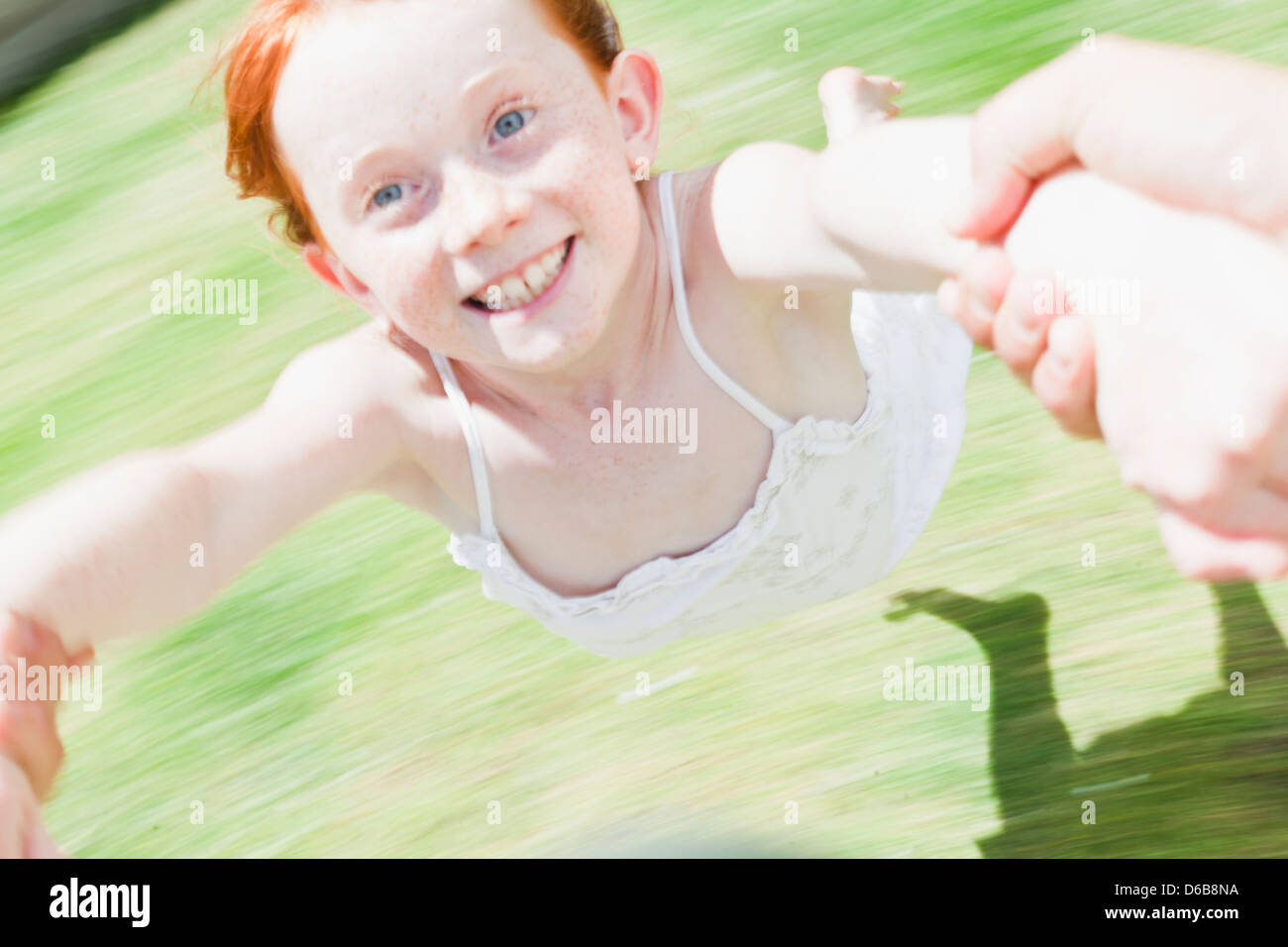 Parent swinging daughter in grass - Stock Image