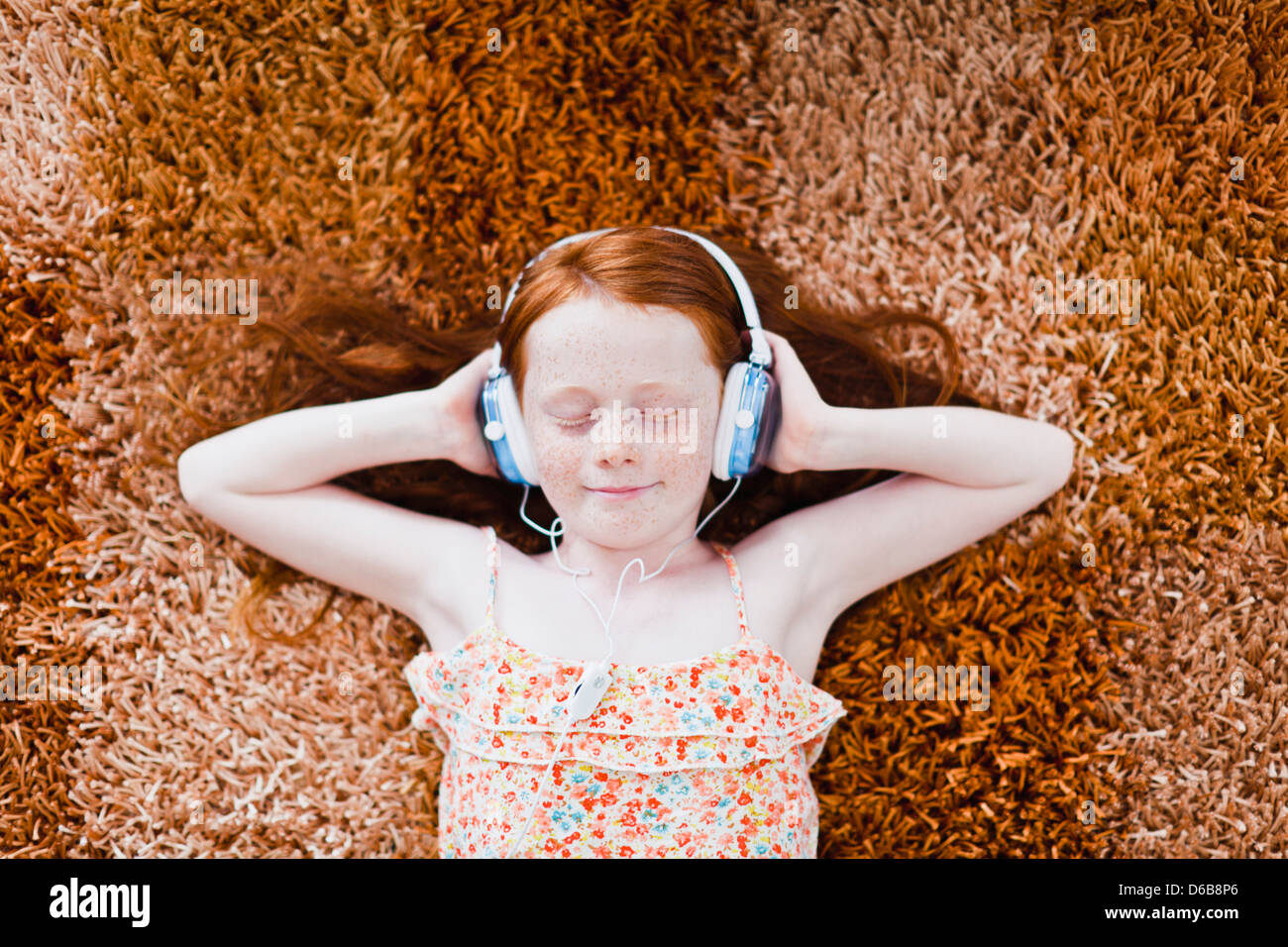Girl listening to headphones on carpet - Stock Image