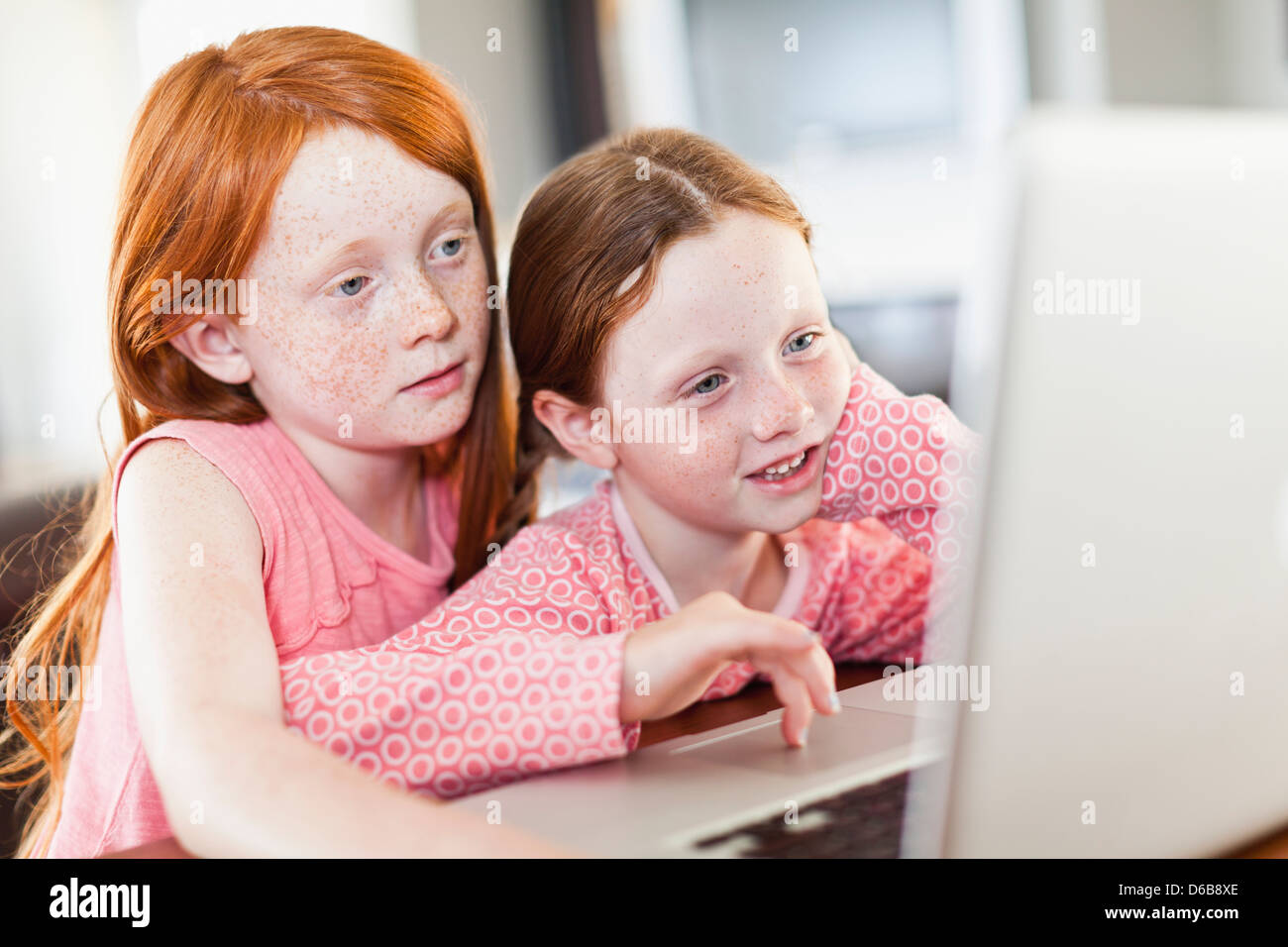 Girls using laptop together - Stock Image