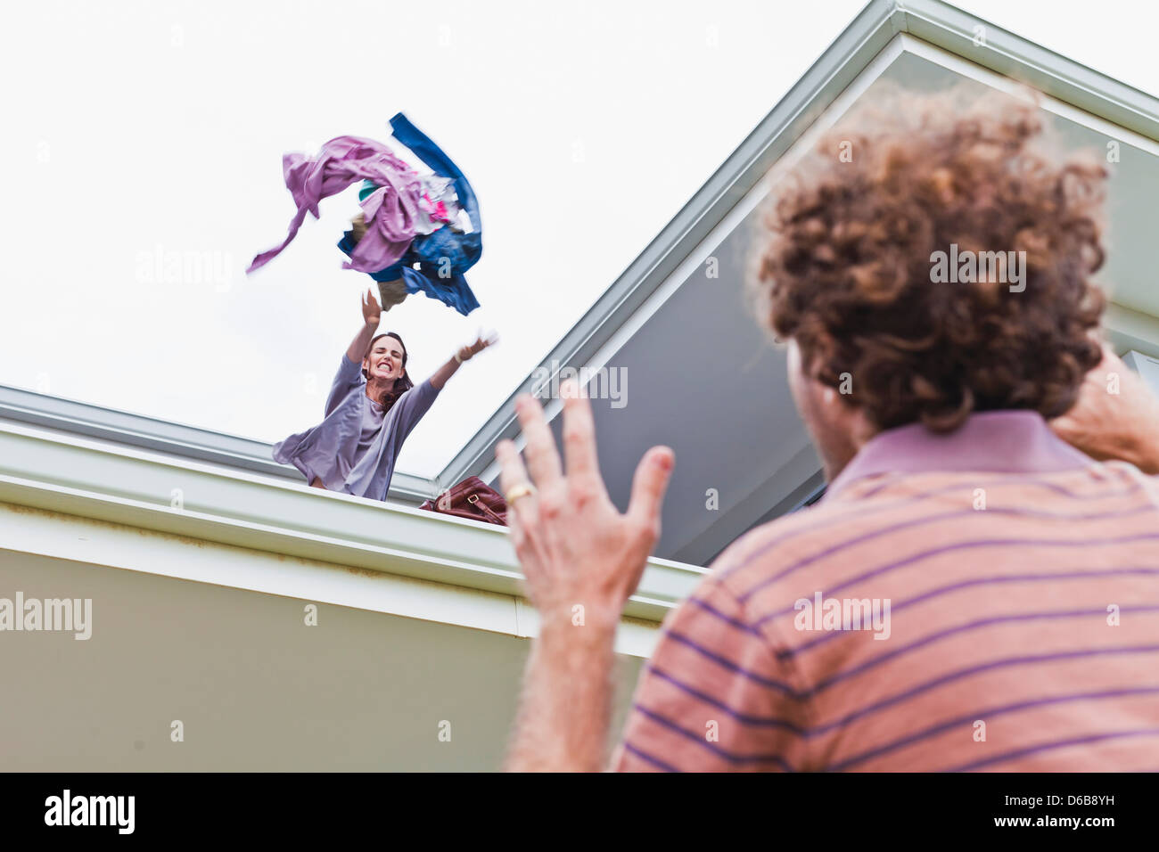 Woman throwing out boyfriends clothes - Stock Image