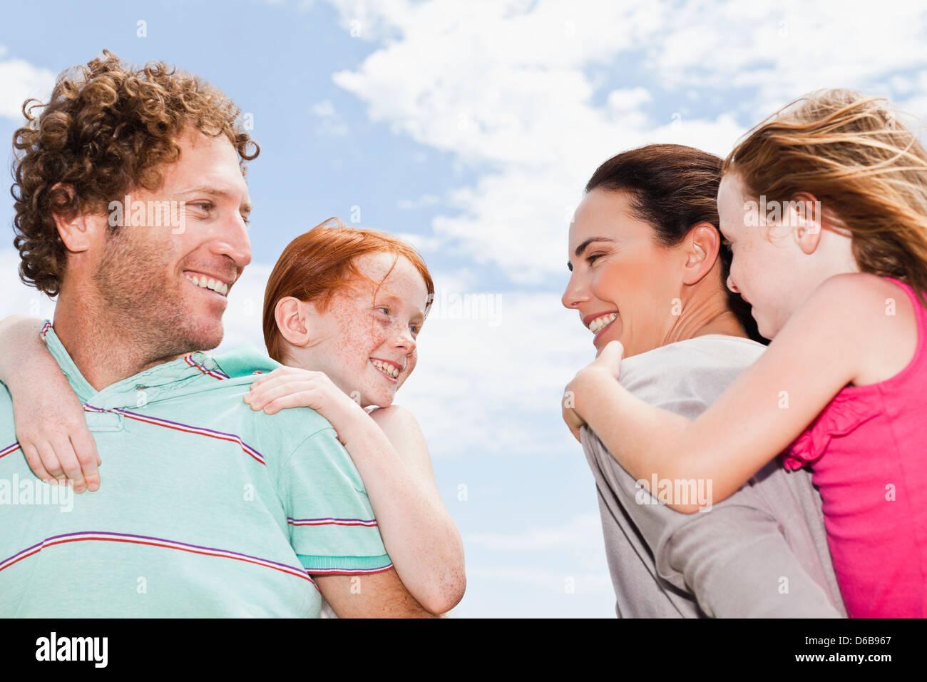 Parents carrying daughters piggyback - Stock Image