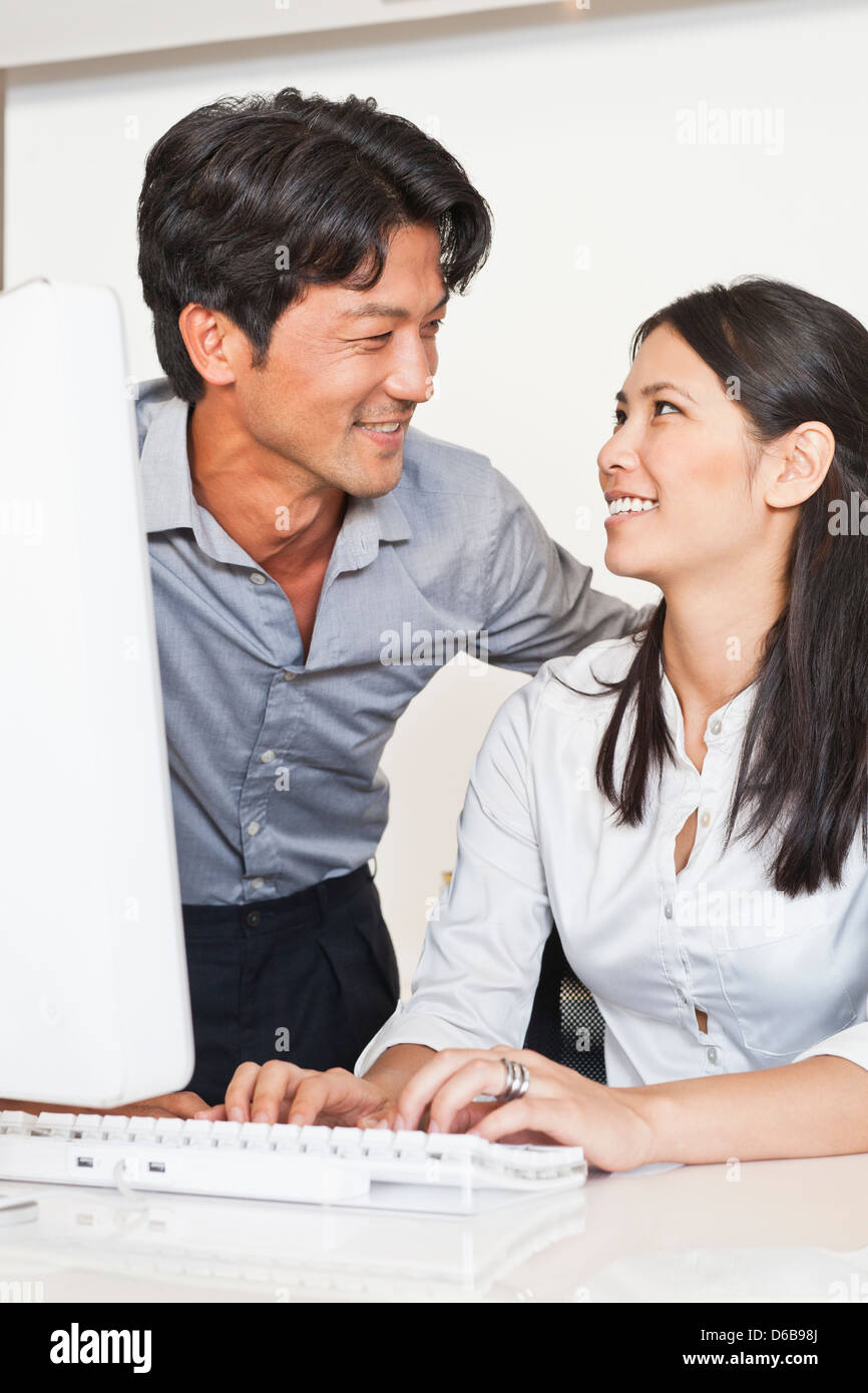 Business people working together at desk - Stock Image