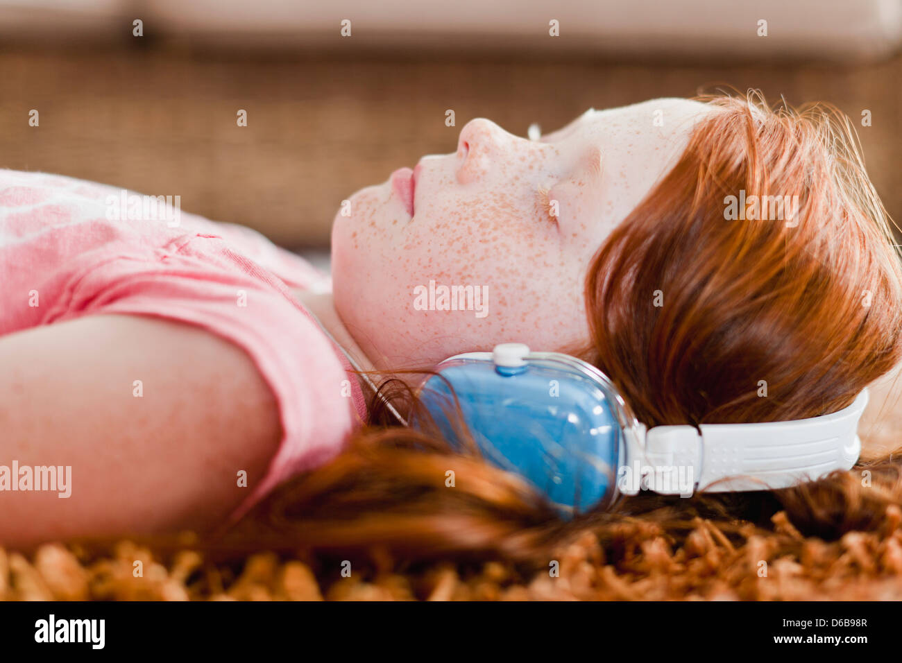 Girl listening to headphones on carpet - Stock Image