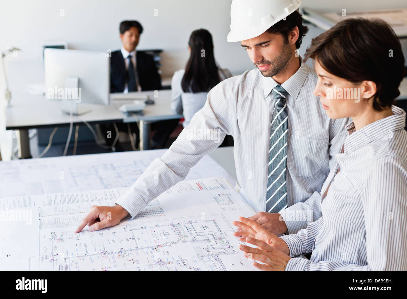 Business people reading blueprints - Stock Image