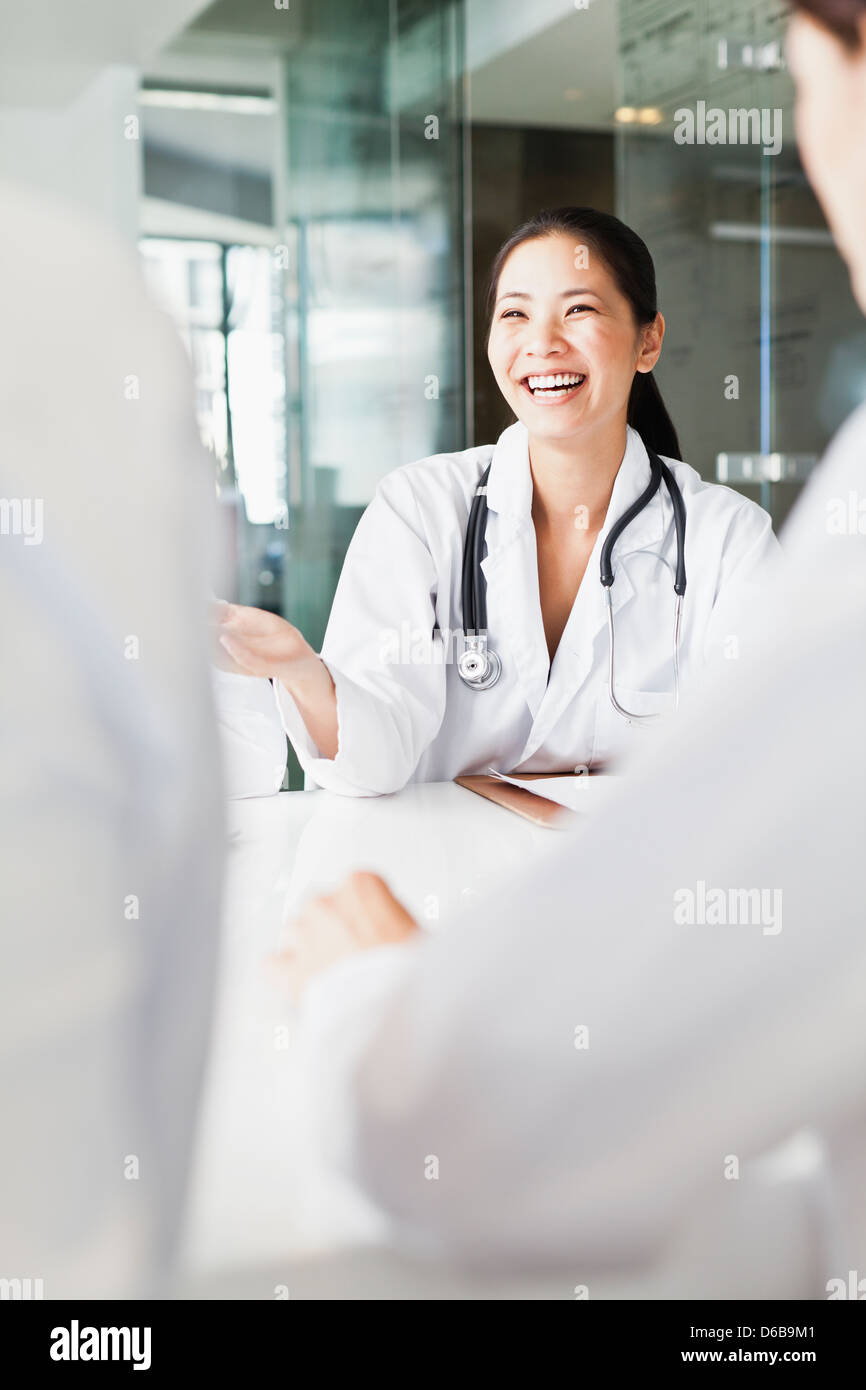 Doctor talking to colleagues in meeting - Stock Image