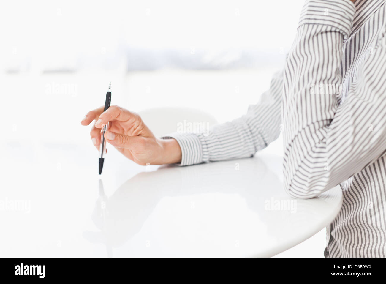 Businessman tapping pen on desk Stock Photo