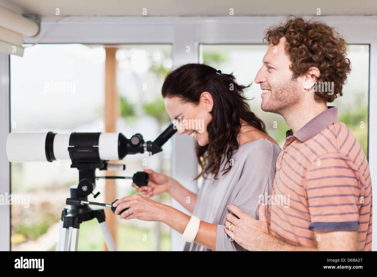 Woman using boyfriends telescope - Stock Image