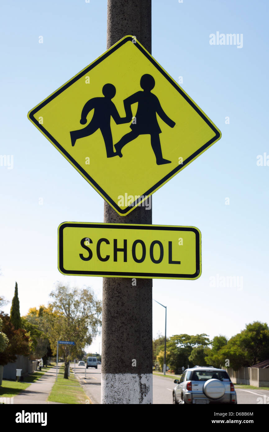 School crossing sign warning drivers they are entering a school zone in urban New Zealand - Stock Image