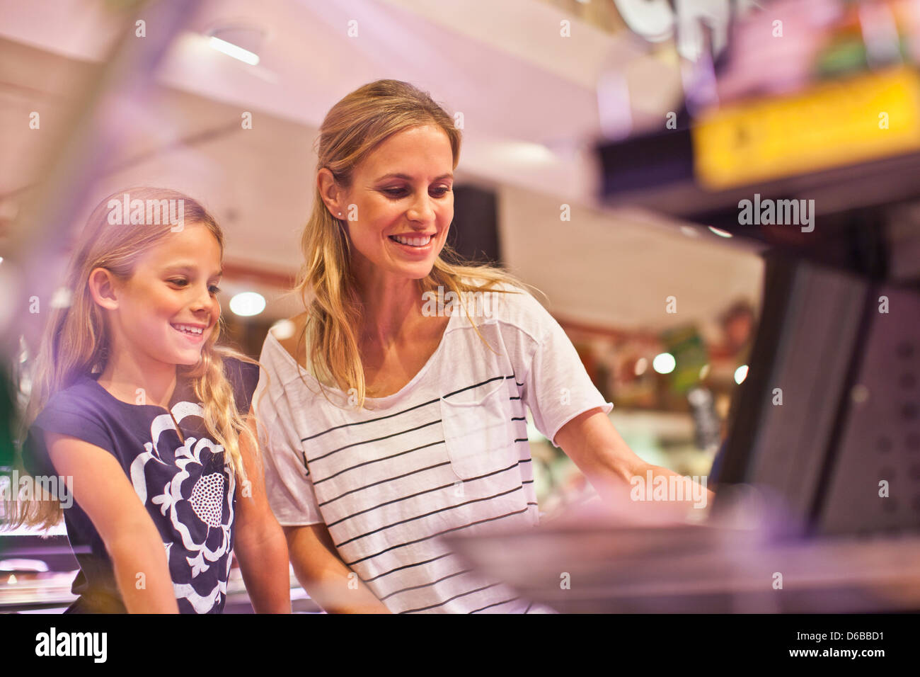 Mother and daughter in grocery store - Stock Image