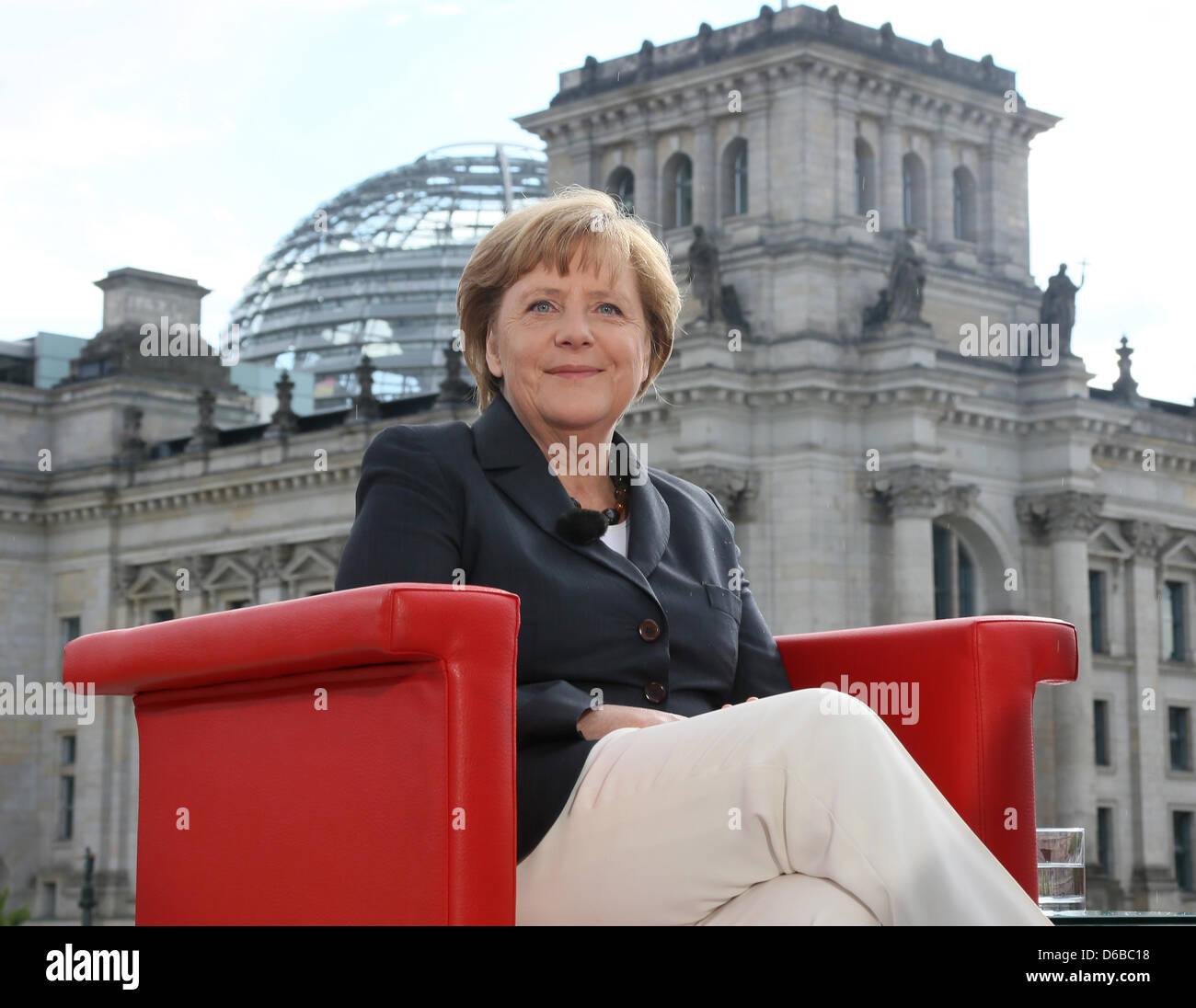 German Chancellor Angela Merkel sits on a red armchair during the summer interview of German broadcasters ARD and Stock Photo