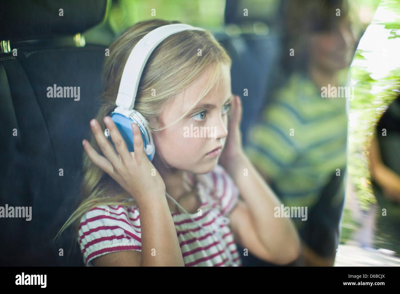 Girl listening to headphones in car Stock Photo