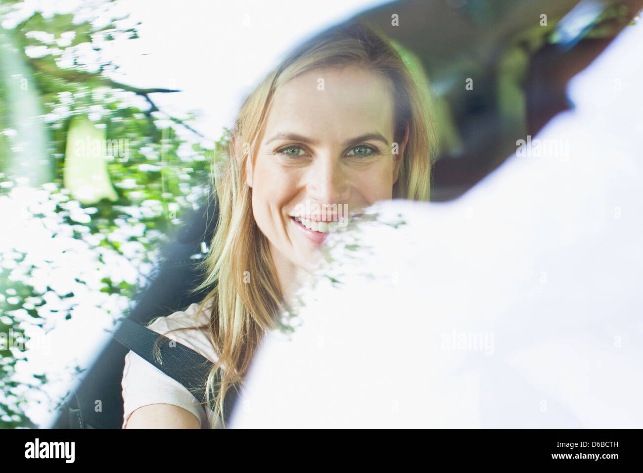 Smiling woman sitting in car Stock Photo