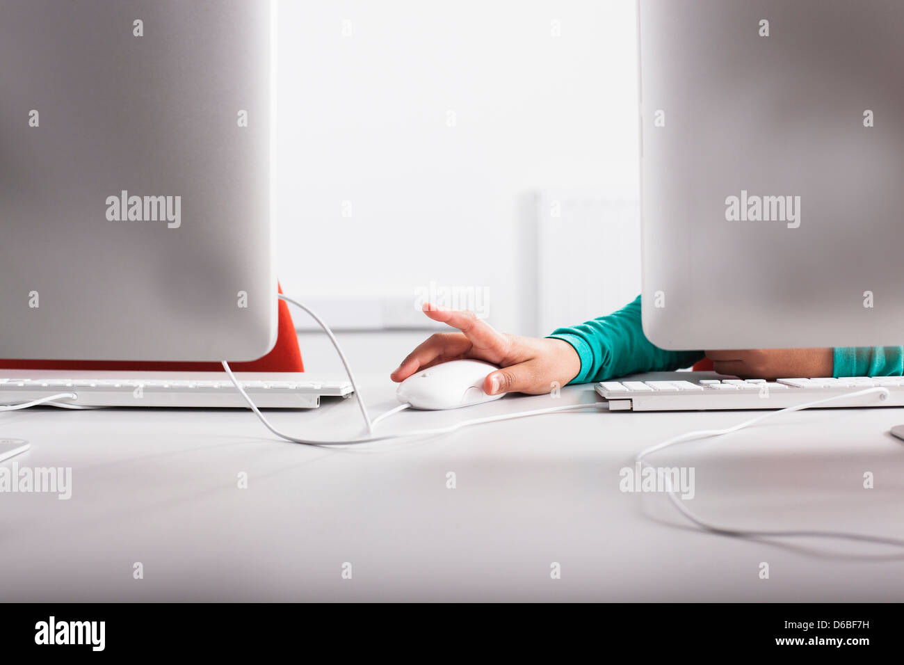 Girl using computer at desk - Stock Image