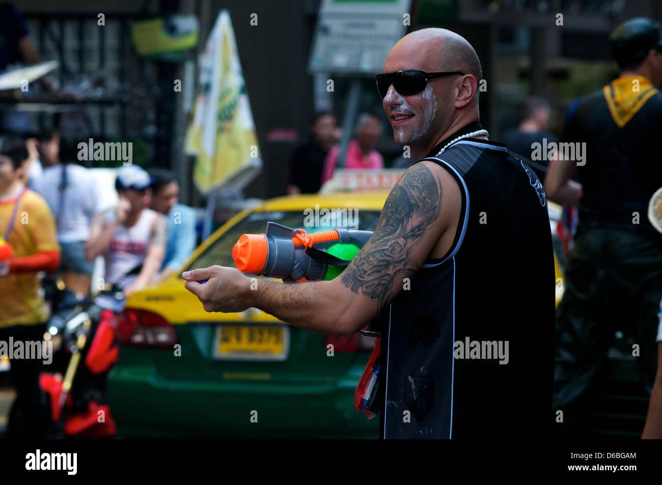 a tourist & his water gun. Bangkok celebrates Songkran, the Thai new year. Bangkok, Thailand. credit: Kraig - Stock Image