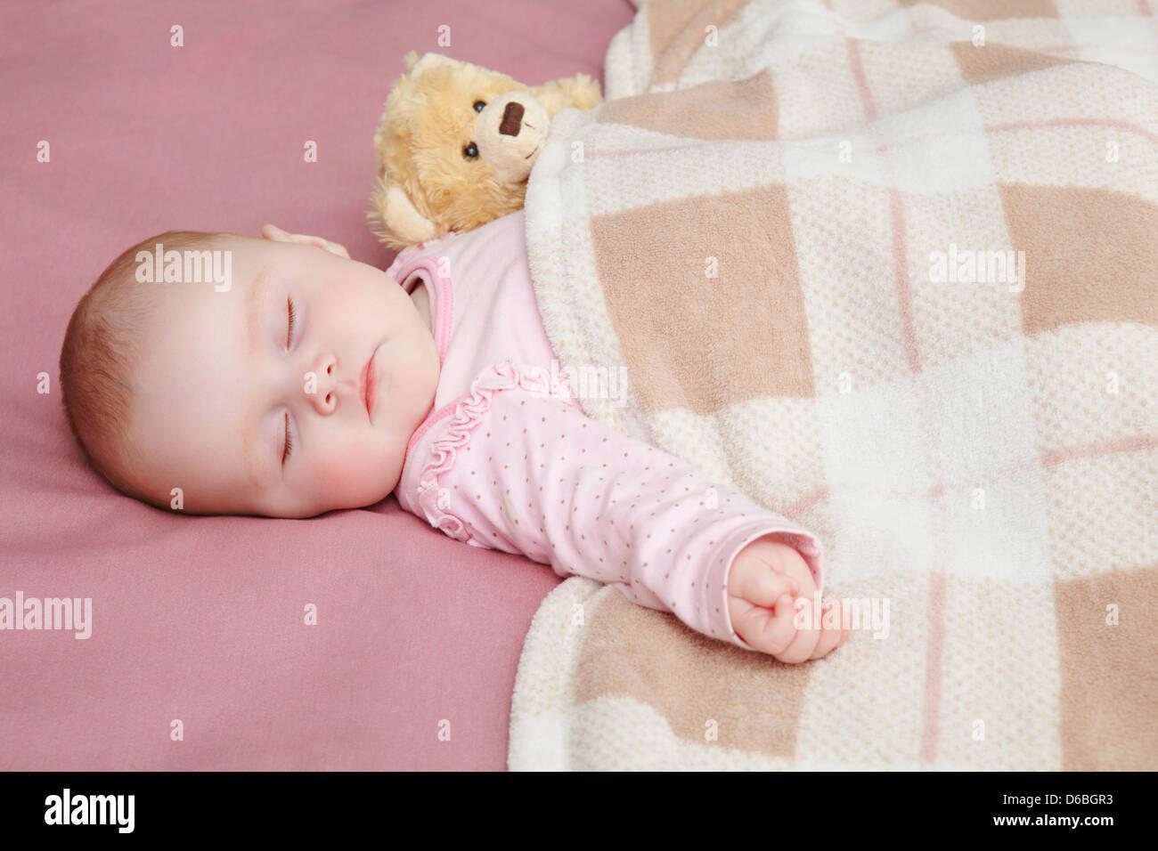 Baby girl sleeping in bed - Stock Image