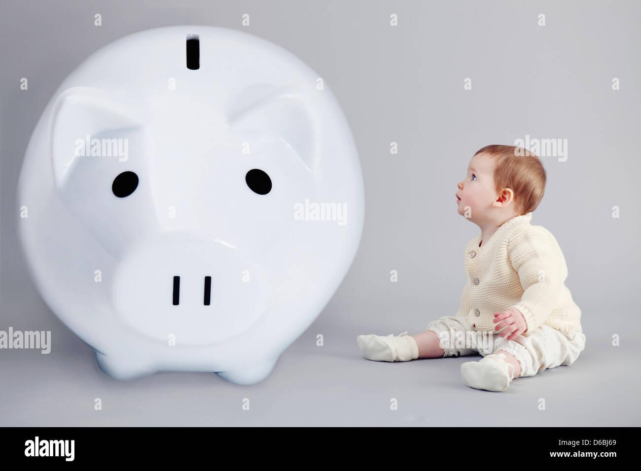 Baby girl examining large piggy bank - Stock Image