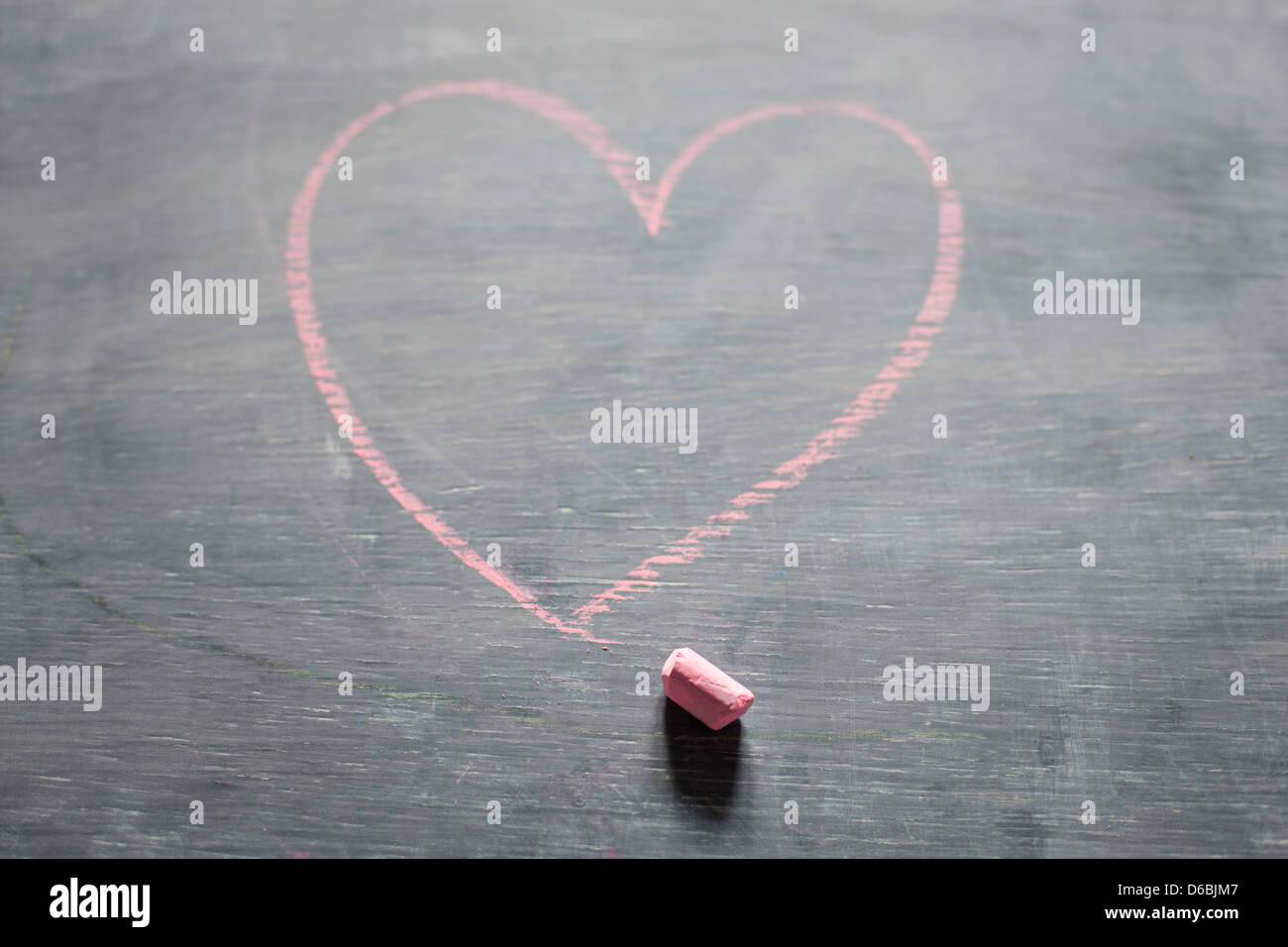 Chalk and heart shape on blackboard - Stock Image