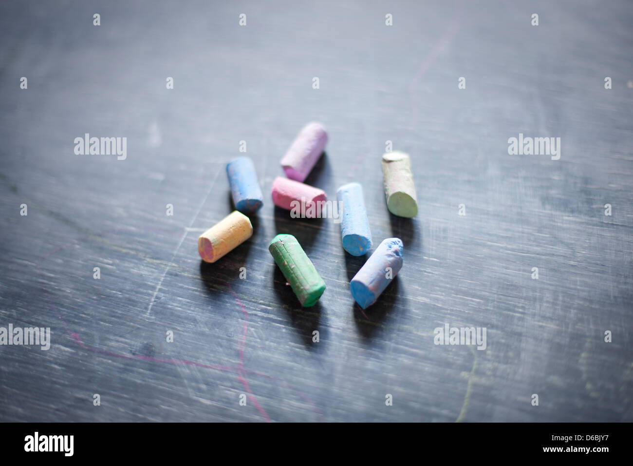 Close up of colorful chalk on blackboard - Stock Image