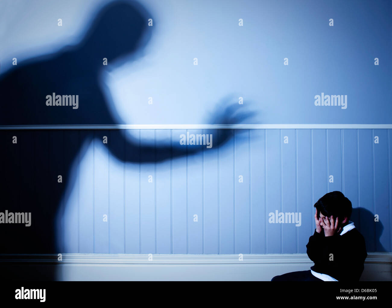 Shadow looming over frightened boy - Stock Image
