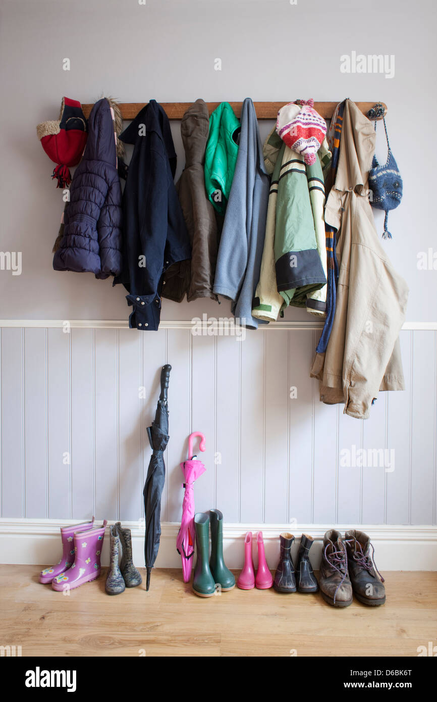 Coats on coat rack with boots - Stock Image
