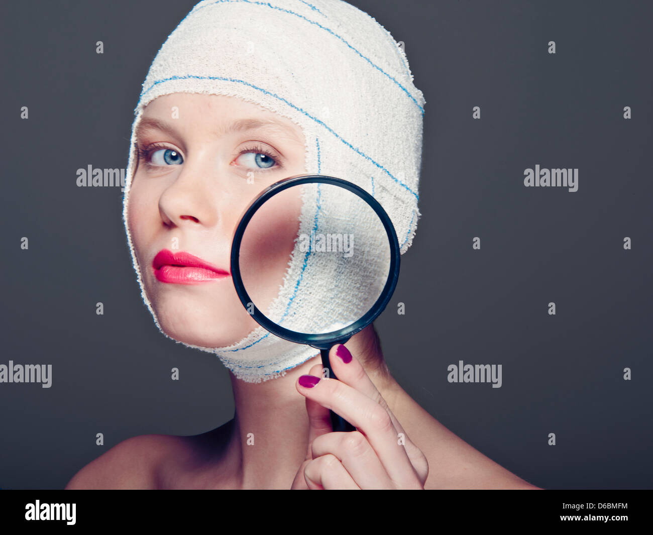 Woman in bandages with magnifying glass - Stock Image