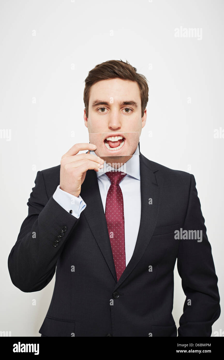 Businessman holding picture over his mouth - Stock Image