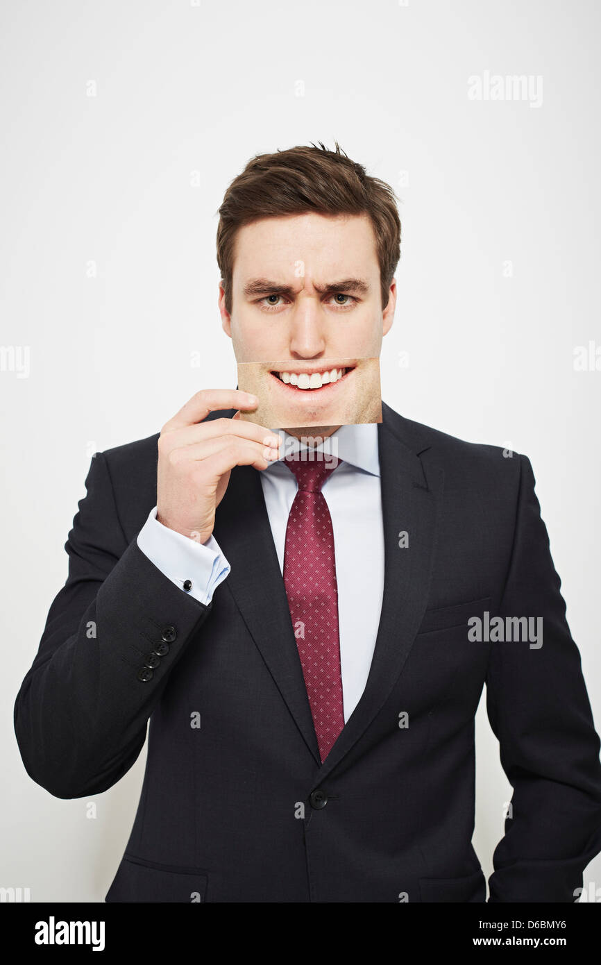 Businessman holding angry picture over his face - Stock Image
