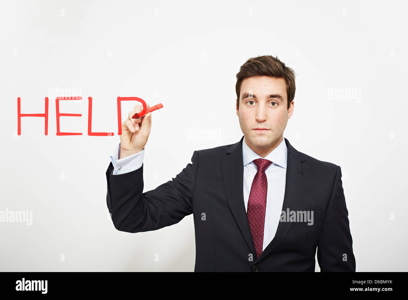 Businessman writing ?help in air - Stock Image