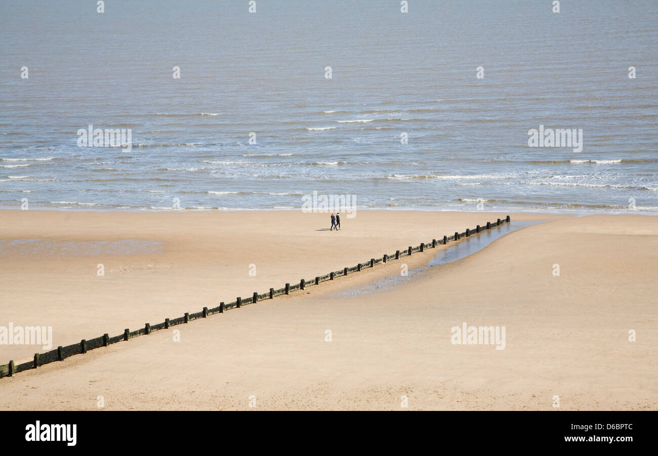 People walking on wide empty sandy beach at Frinton on Sea, Essex, England - Stock Image