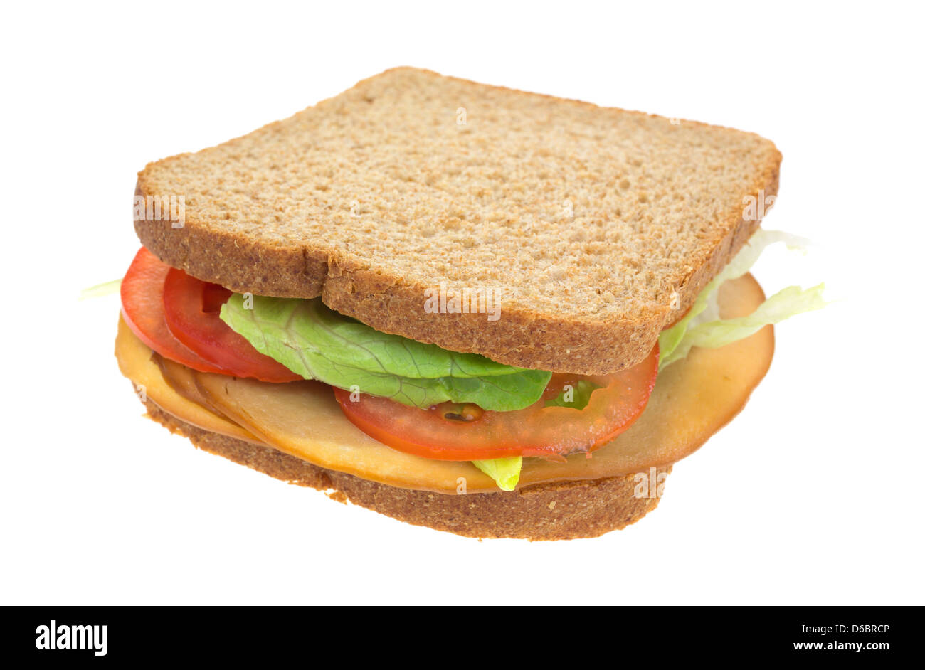 A whole wheat sandwich with tofu smoked turkey tomatoes and lettuce. - Stock Image