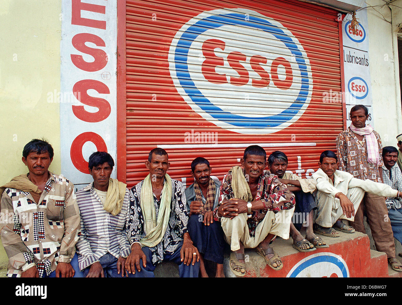 Under an advertisement for the multinational company Esso, Indian day labourers are waiting for work in a street - Stock Image