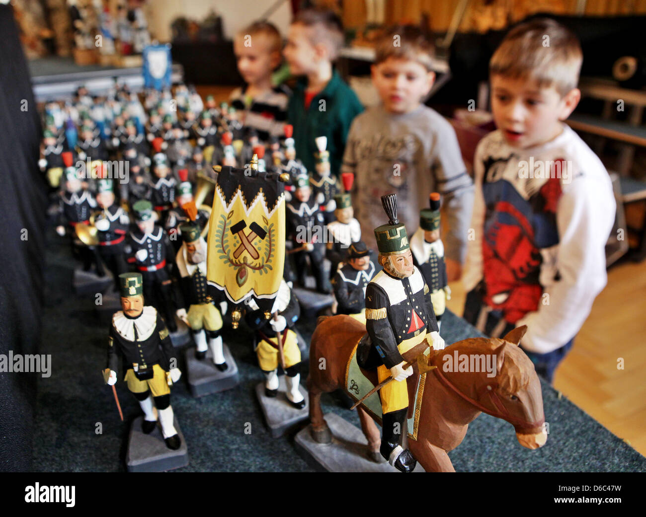 Children view carved figures at the exhibition 'Carving Region Ore Mountains' in Annaberg-Buchholz, Germany, - Stock Image