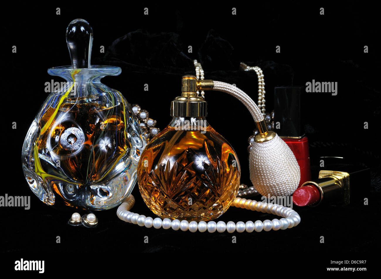 Perfume atomiser bottle, Perfume bottle with stopper and jewellery against a black background. - Stock Image