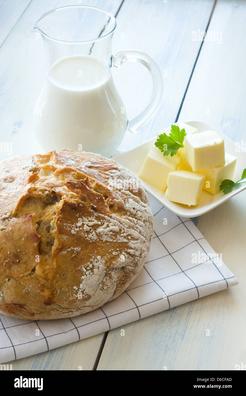 Homemade bread, milk in glass jug and butter - Stock Image